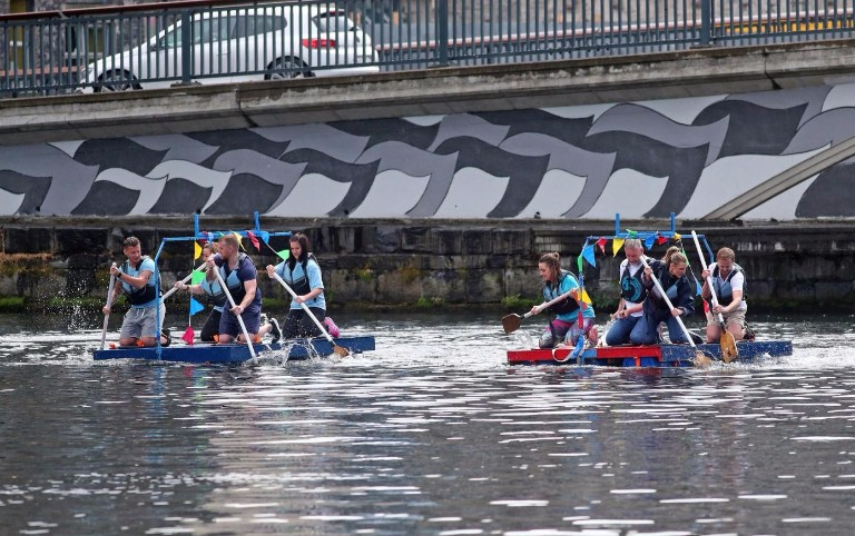 Racin in the Basin. The local Bank of Ireland and Credit Union battle it out in the second heat of the raft challenge. The mural in the back ground was painted by volunteers from the Docklands Business Forum two weeks before the event.