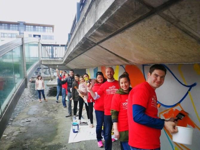 Volunteers painting the new mural on the McMaon Bridge